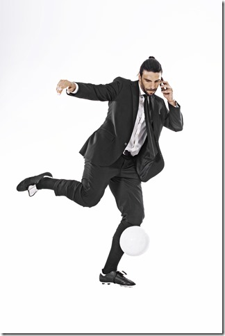 Business man kicking a ball while calling
